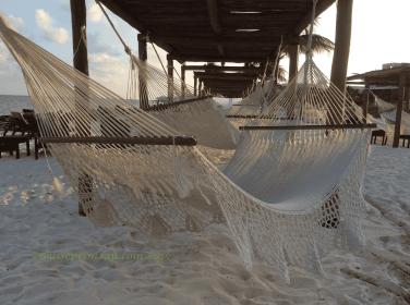 row of hammocks on the beach