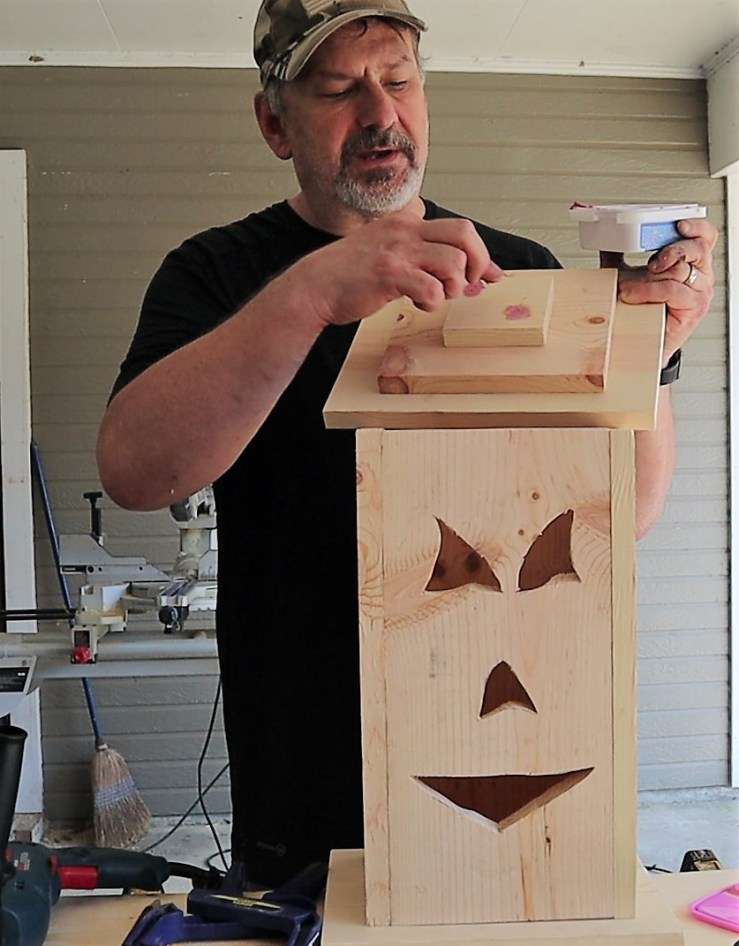 Putting wood filler into holes on top of Halloween DIY Jack-o-Lantern Light-up box.