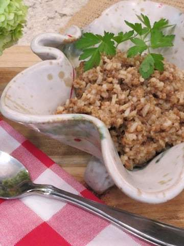Rice dressing in a serving dish with red checkered napkin and spoon.