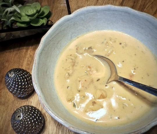 A spoon in a blue bowl of seafood bisque with lumps of crab and shrimp. on a wooden table with small salt and pepper shakers.