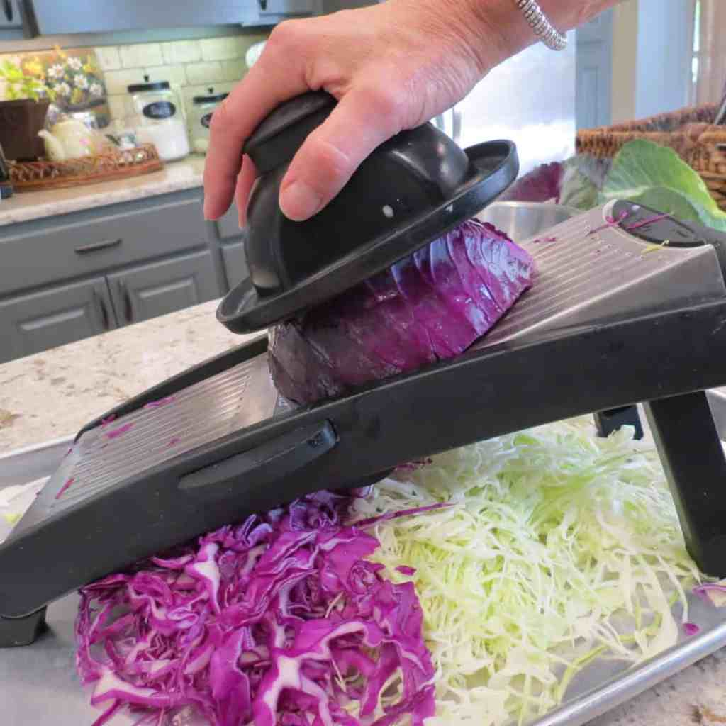 Slicing cabbage with mandolin for Southern Louisiana Coleslaw.