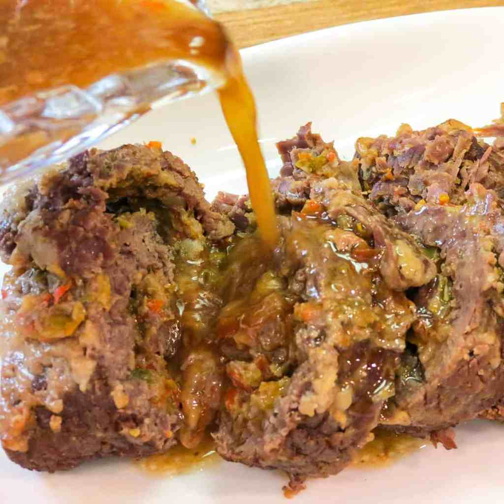 Instant Pot Rolled Round Steak sliced on a white platter with juice being poured over it.