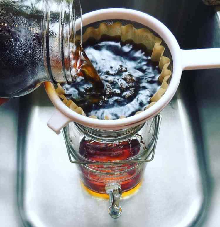 Cold brew coffee being poured into a strainer.