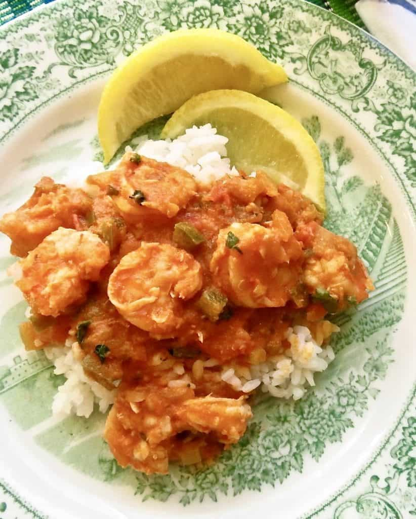 Shrimp creole on a bed of white rice with lemon for garnish