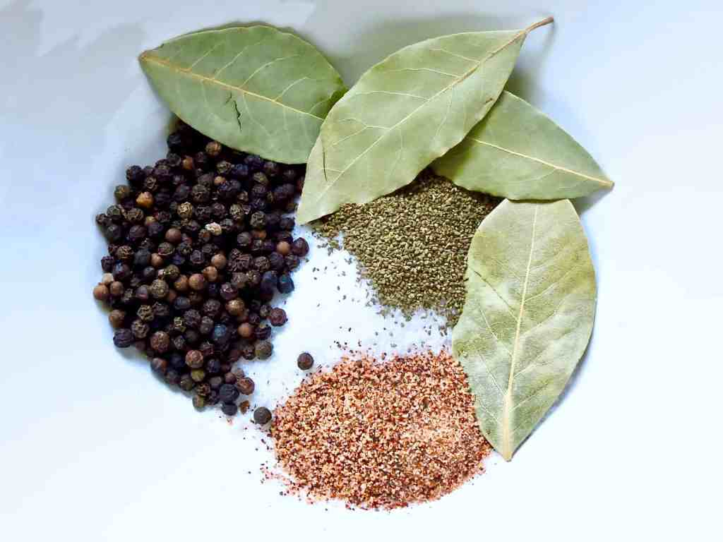 Peppercorns, bay leaves, salt, and other seasonings in a white bowl.