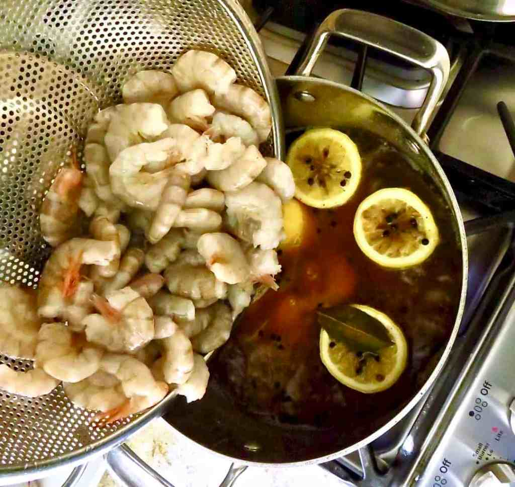 Fresh shrimp poured into a pot of boiling water with lemon halves and seasonings.