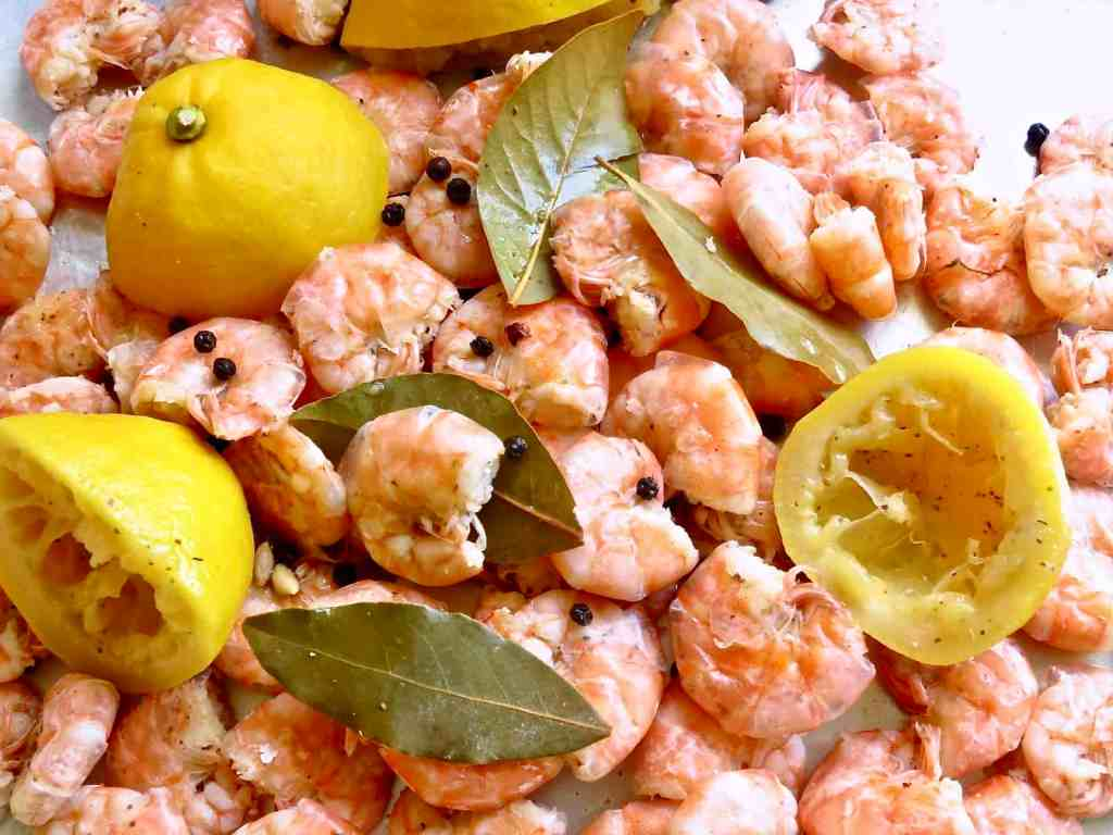 Boiled shrimp and lemon halves and bay leaves spread out on a pan..