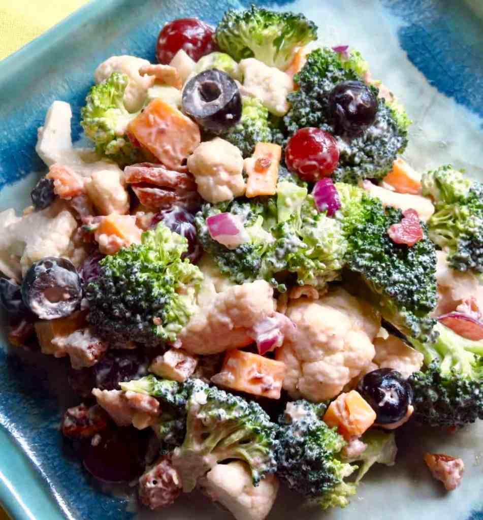 A blue dish filled with broccoli cauliflower salad