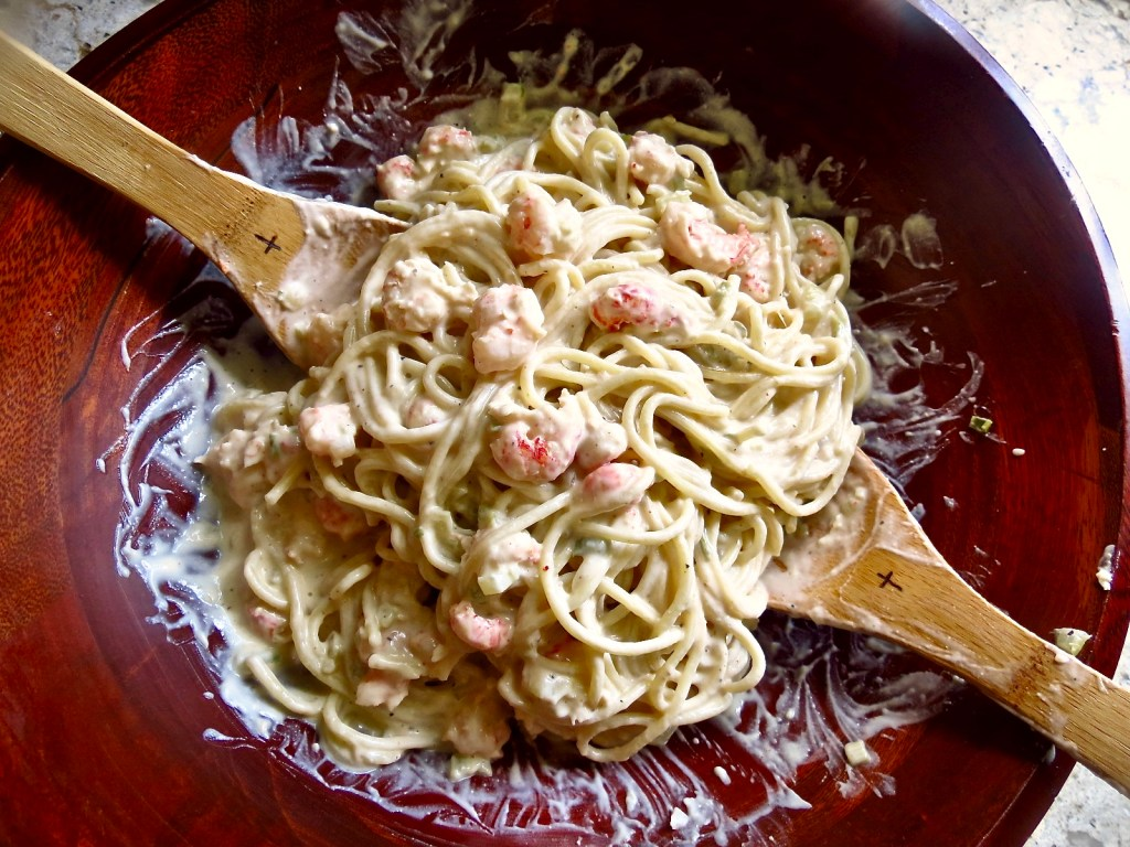 Shrimp And Crawfish Pasta in wooden bowl with wooden serving spoons