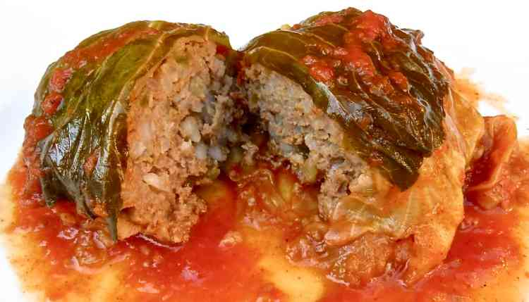 One Classic Cabbage Roll in a white plate in tomato sauce.