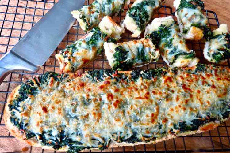Loaf of spinach bread and cut up pieces on a rack with a knife.