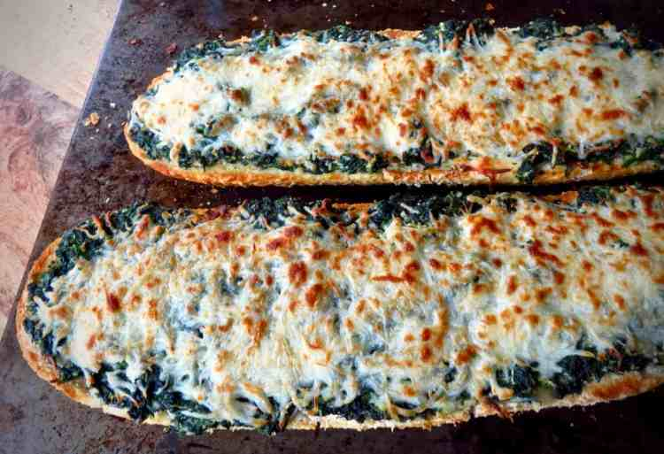 Two half loves of Easy Spinach Bread with cheese browned from the oven.