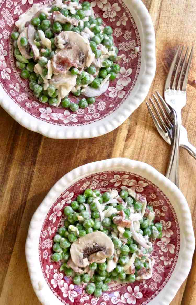 Pea Salad, The Forgotten Side Dish in 2 red and white toile bowls with forks on a wooden board.