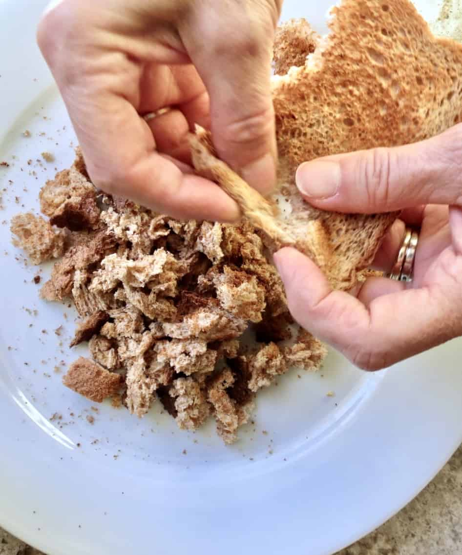 Two hands breaking up whole wheat toast to make bread crumbs for cornbread dressing.