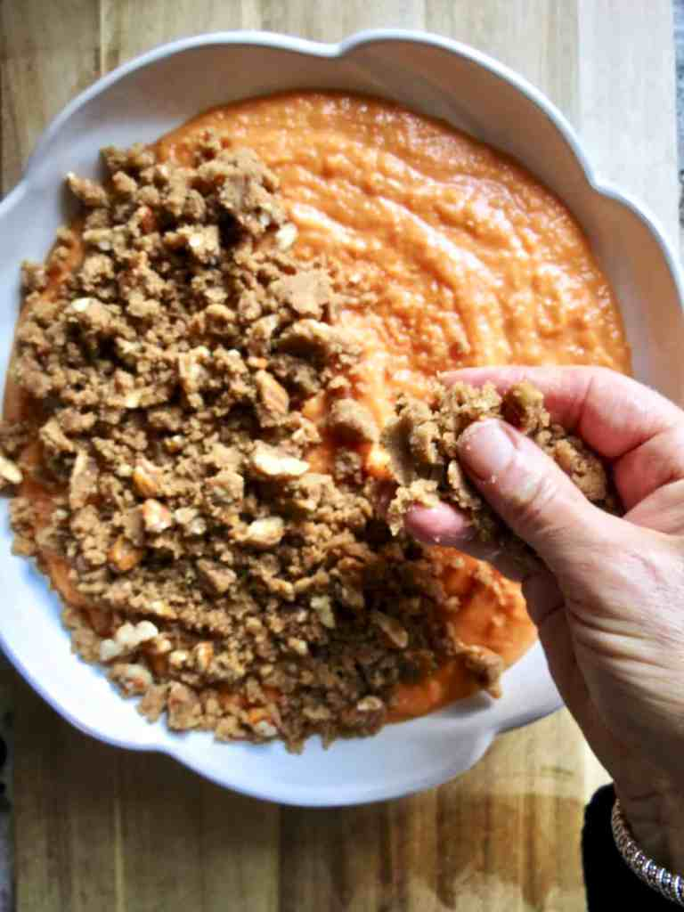 Brown sugar nut topping being put on top of Fresh Sweet Potato Casserole.