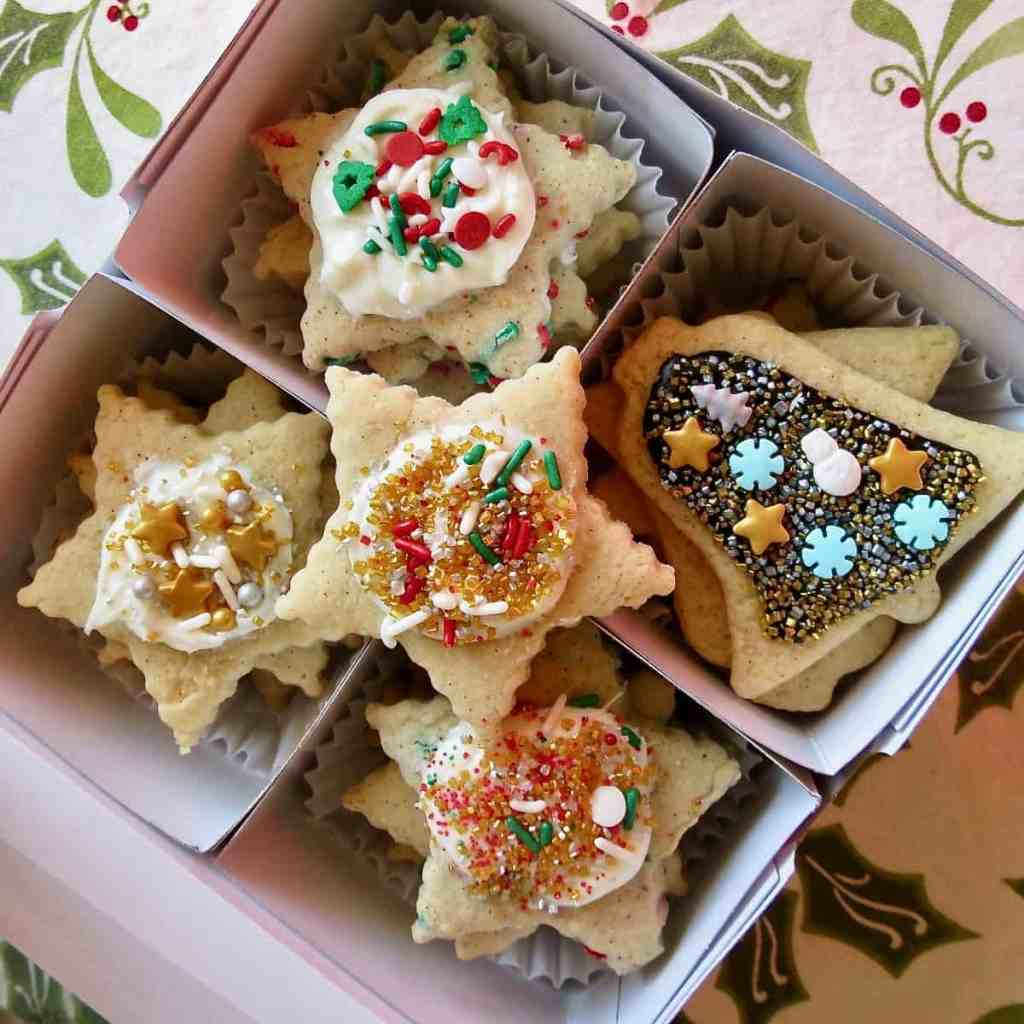 A box of cutout Sugar Cookies decorated in with assorted sprinkles.