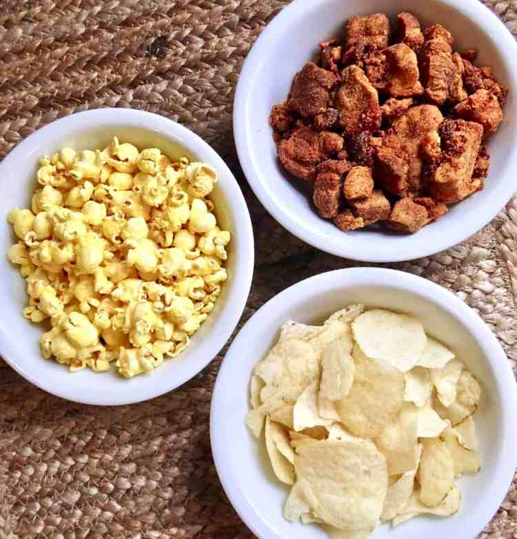 Three white bowls of potato chips, popcorn, and cracklings for Easy Appetizers To Tease And Appease The Appetite.