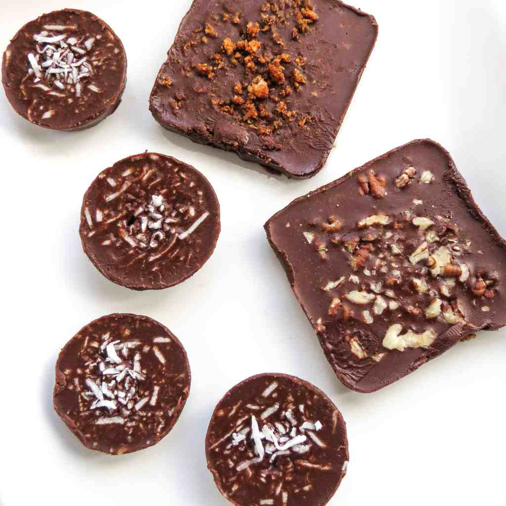 Square and round chocolate Fat Bombs on a white plate.