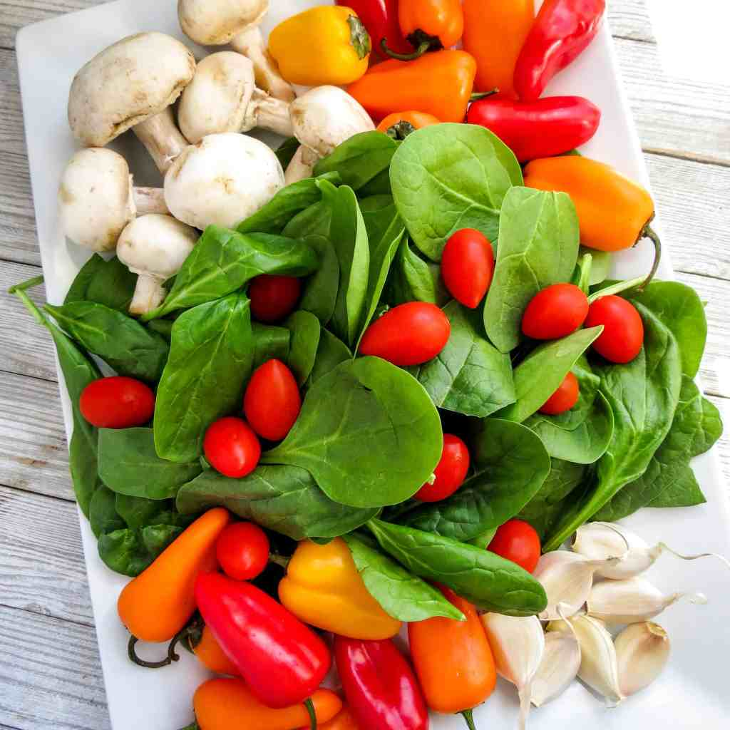 Fresh spinach, mushrooms, colored mini peppers, grape tomatoes, and garlic on a white platter for Spinach Medley, A Healthy Spinach Side Dish.