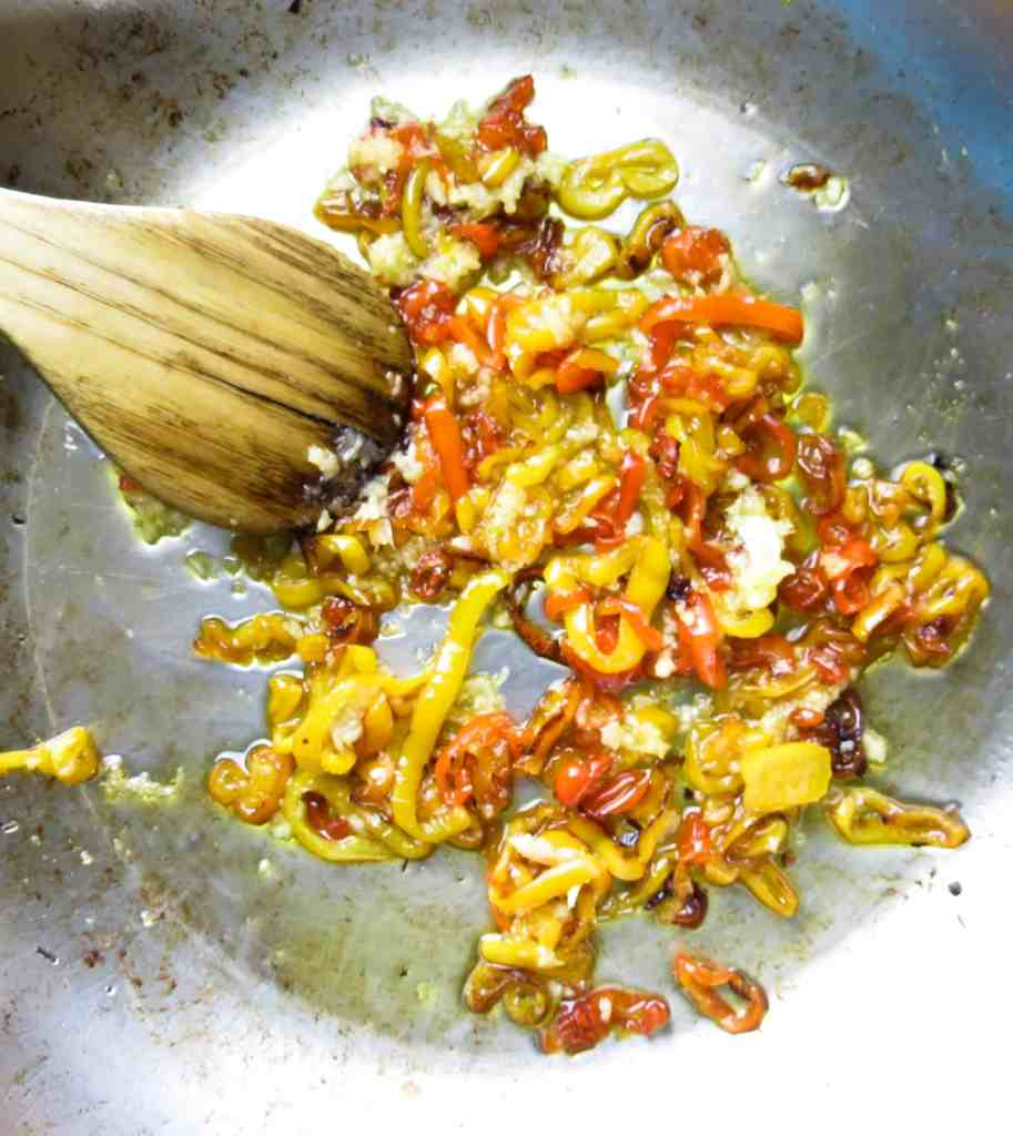Sautéed sweet peppers in a pan with a wooden spoon.
