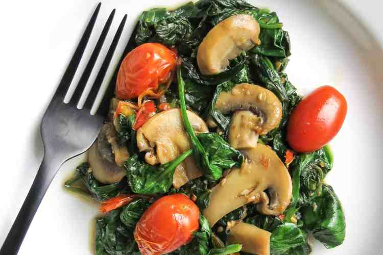 A white bowl with a black fork holds a serving of sautéed spinach, Mushrooms, grape tomatoes, and sweet peppers for a Spinach Medley, A Healthy Spinach Side Dish.