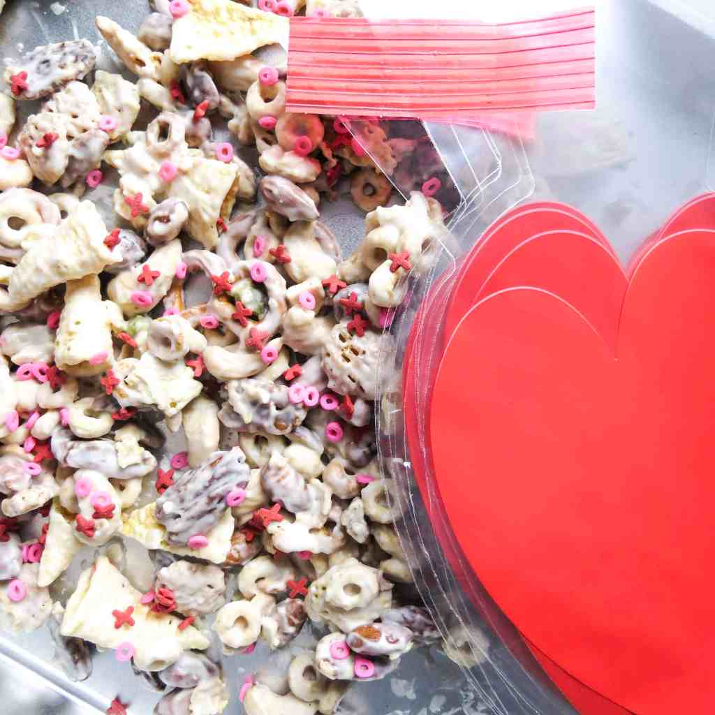 Valentine Candy Crunch spread out on an aluminum pan with heart plastic bags and ties.