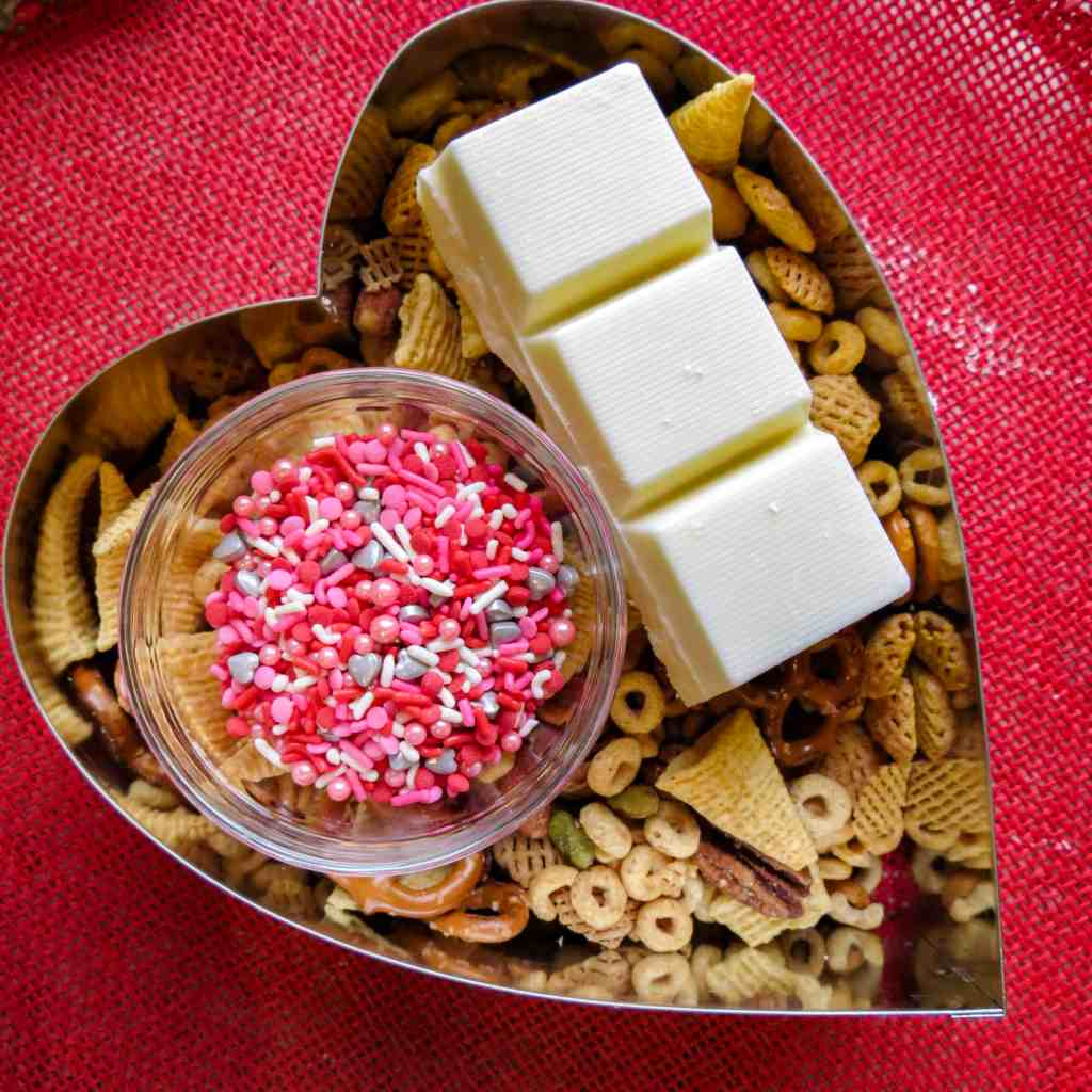 Ingredients of cereal, sprinkles, and white chocolate in a heart shape mold on a red placemat.