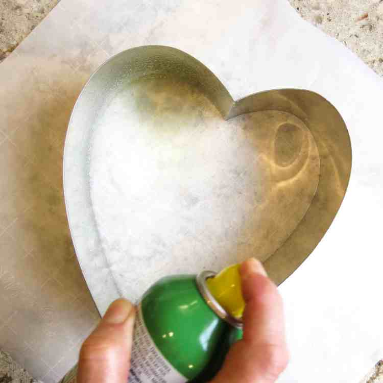 Spraying vegetable spray in a heart shaped tin mold.