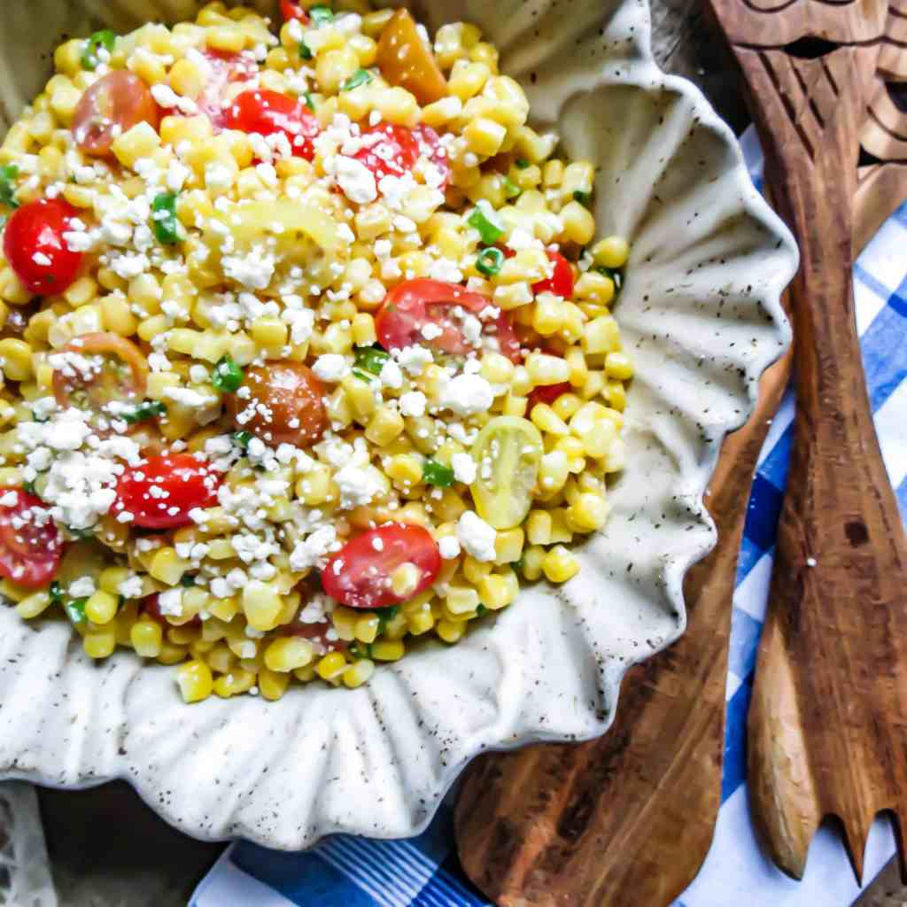 A light gray bowl of pottery filled with Corn Salad With Tomatoes on a blue and white towel with wooden salad server fork and spoon.