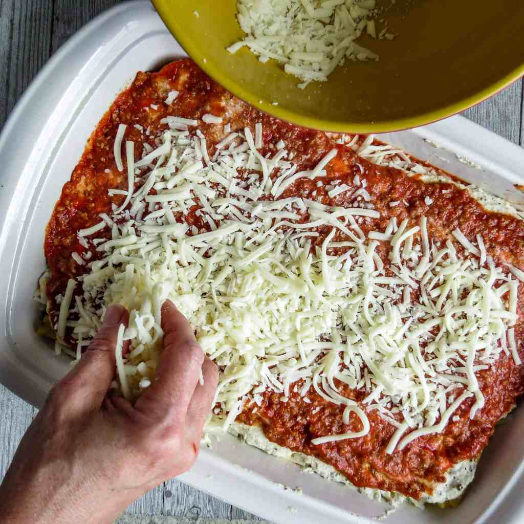 A white casserole dish with layer of mozzarella onto sauce for Easy Lasagna Recipe, Step-By-Step.