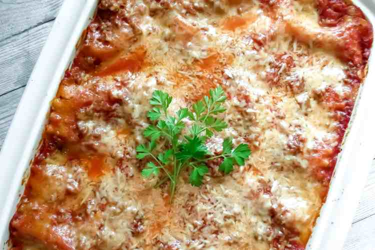A white casserole dish with a cooked Easy Lasagna Recipe, Step-By-Step garnished with fresh parsley in the center.