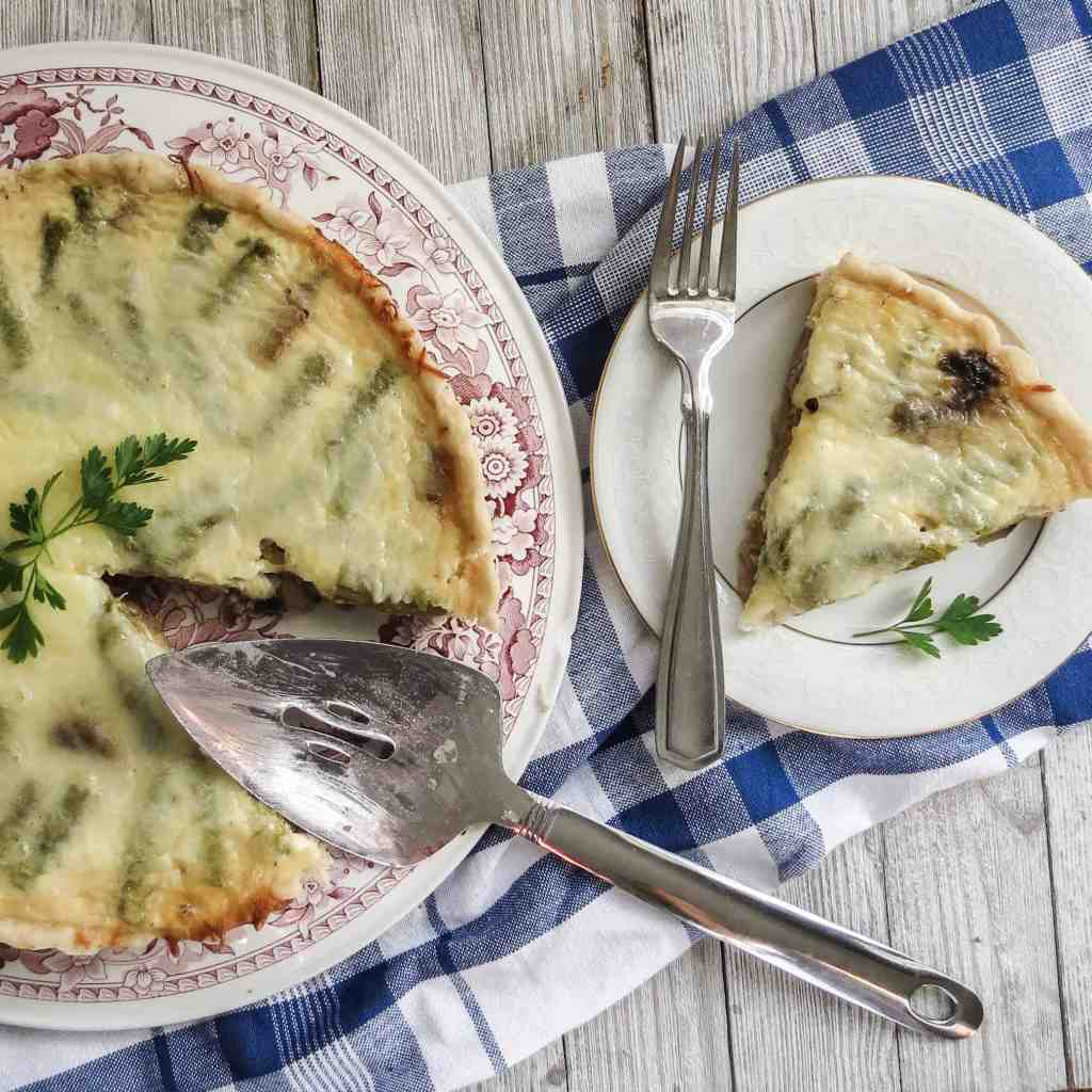 A slice of quiche cut on a white plate with a whole quiche with cake cutter on a gray board with a blue and white plaid towel.
