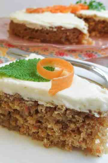 A slice of single layered Glazed Carrot Cake topped with a carrot curl and mint leaf on a white china plate.