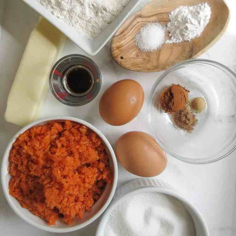 Ingredients for a Glazed Carrot Cake on a white tray.