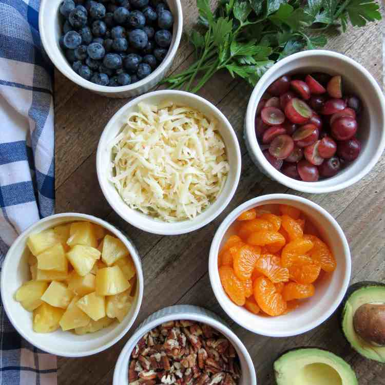 Six white bowls with fruit, nuts, and cheese on a wooden board with parsley and a cut avocado.