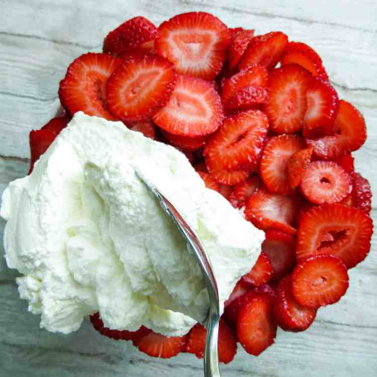 Sliced strawberries in a glass bowl over a wooden tray with cream spooned on top.