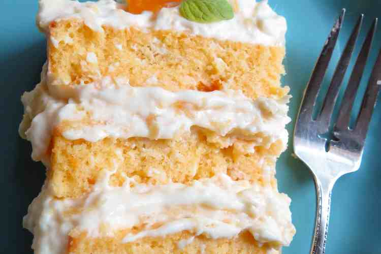 Slice of 3 layer Mandaliscious Mandarin Orange Cake on a blue plate with a fork.