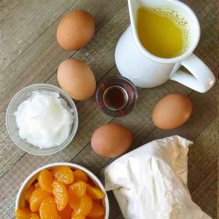 Four eggs, a white pitcher of orange juice, a bowl of mandarin oranges, bag of cake batter, a bowl of coconut oil, and vanilla flavoring on a wooden bowl.