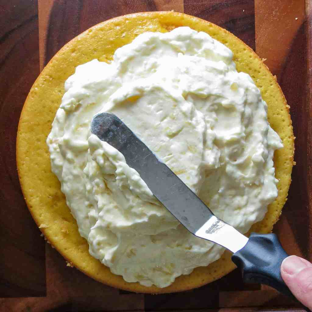 A round yellow cake layer frosted with a creamy filling with a slanted spatula on a wooden board.
