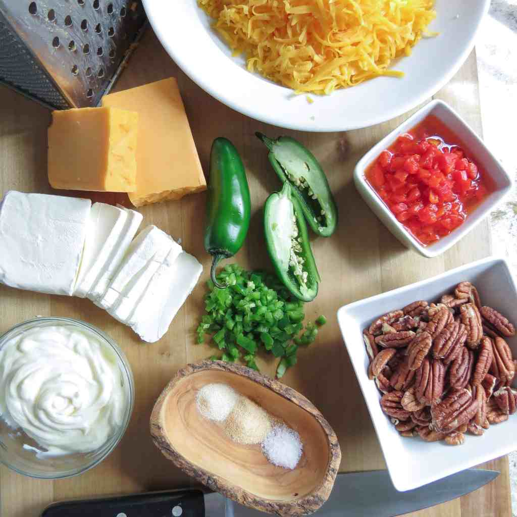 Bowls of grated cheese, pecans, and pimentos on a wooden board with cheeses, jalapeño peppers and cheese grater on a. wooden board.
