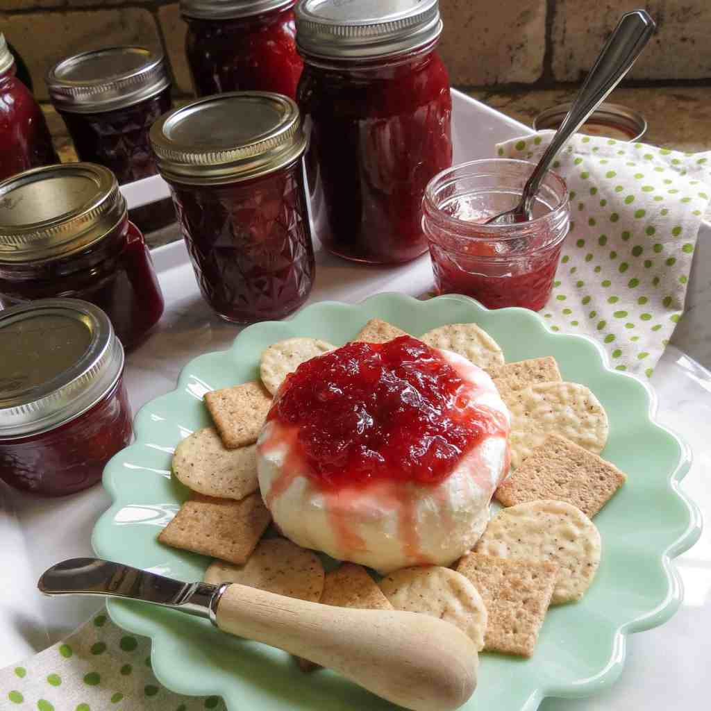 Jars of fig jam with a plate of crackers and cream cheese topped with fig jam.