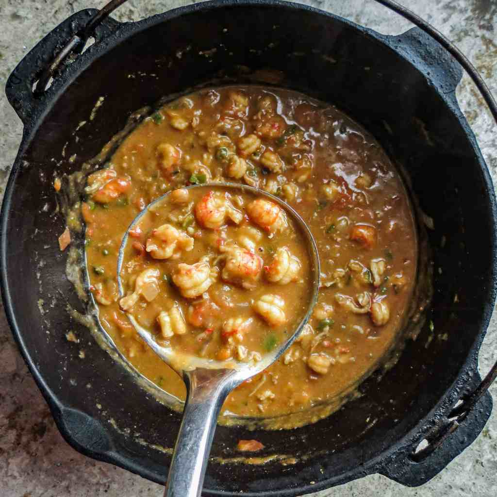 A black iron potful of crawfish stew and a ladle over it filled with the stew.
