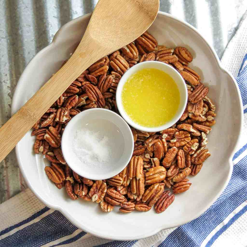 A bowl of pecans with a spoon and ingredients of butter and salt.