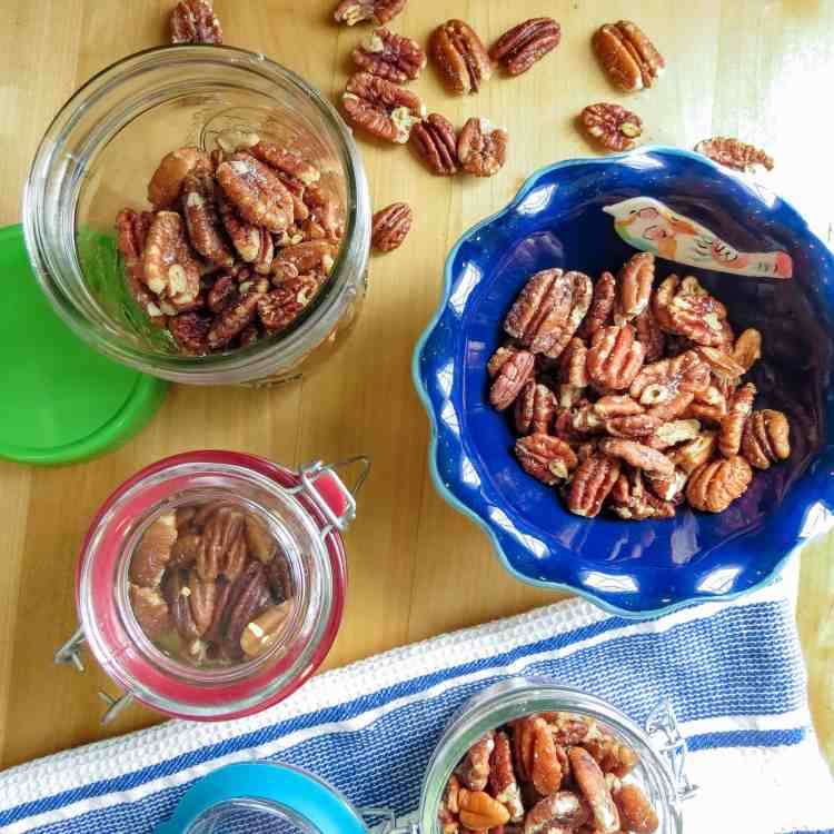 Roasted pecans in different containers for storage and serving.