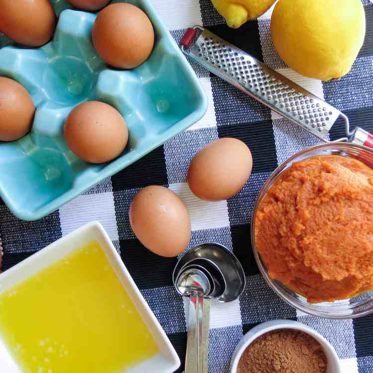Eggs, pumpkin, lemons, melted butter and spices on a black and whit buffalo checked cloth.