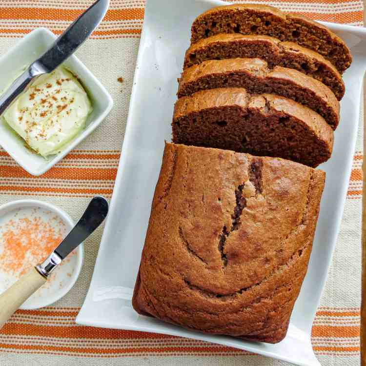 A loaf of sliced pumpkin bread with a bowl of butter and icing beside it.