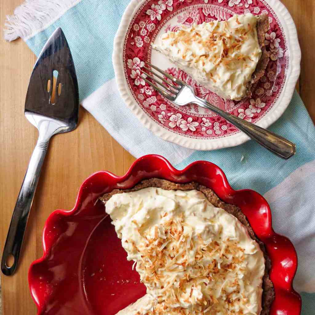 A piece of Low Carb Coconut Pie on a plate, a pie in a red pie pan with a pie server.