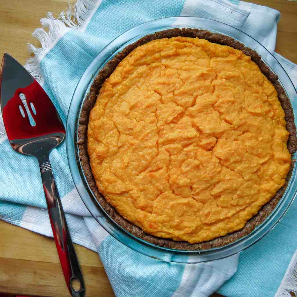 A sweet potato pie with a pie cutter.