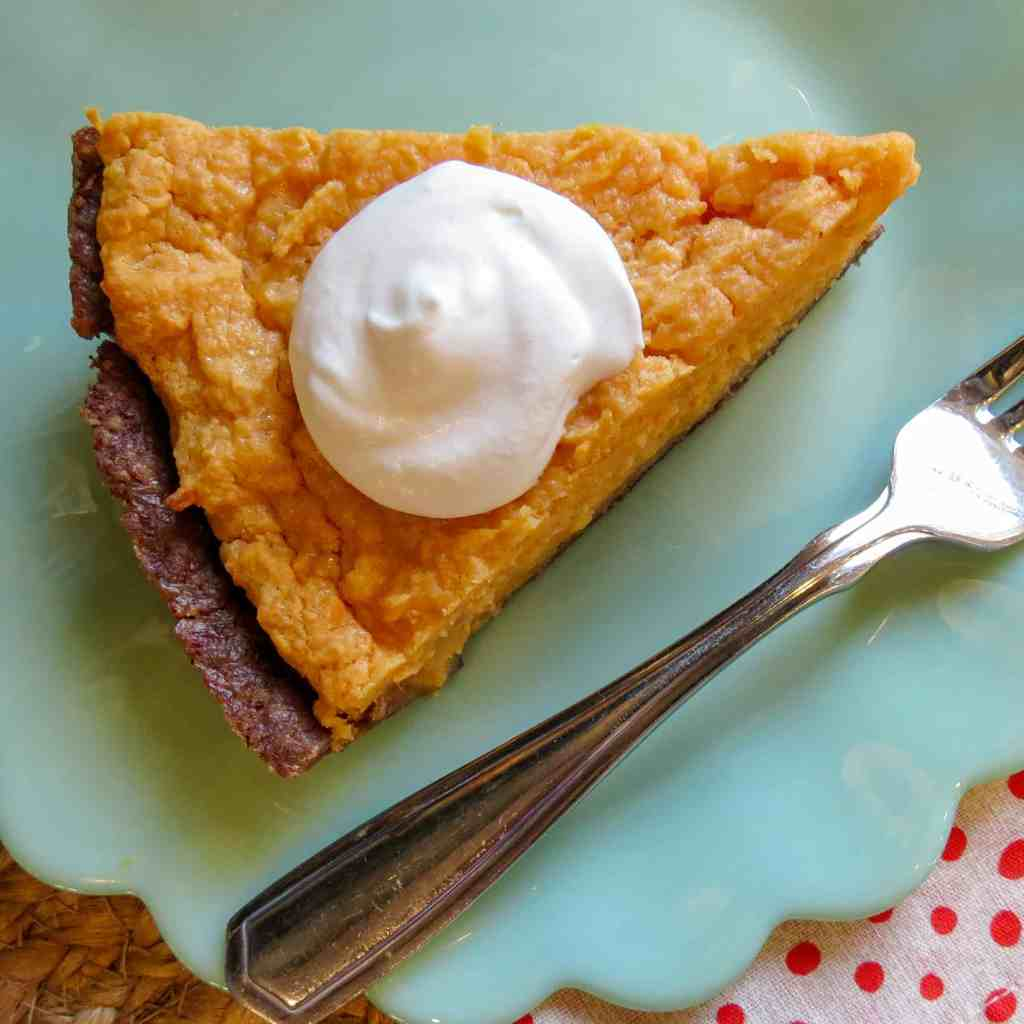 A piece of No Sugar Sweet Potato Pie with a dollop of whipped cream.