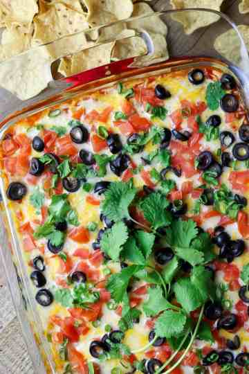 A dish of cheesy dip with fresh celantro on top.